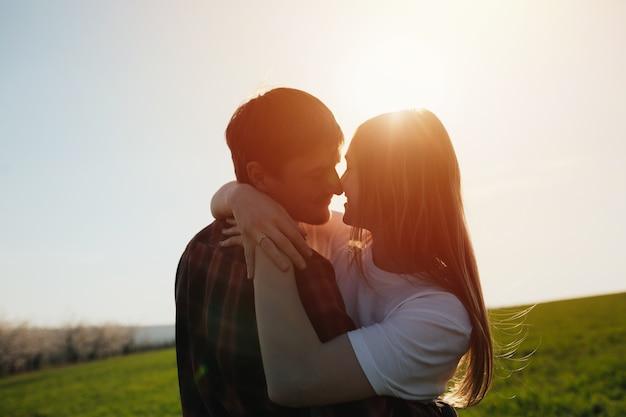 Portrait de gros plan ensoleillé de jeune couple heureux étreindre sur la journée ensoleillée.