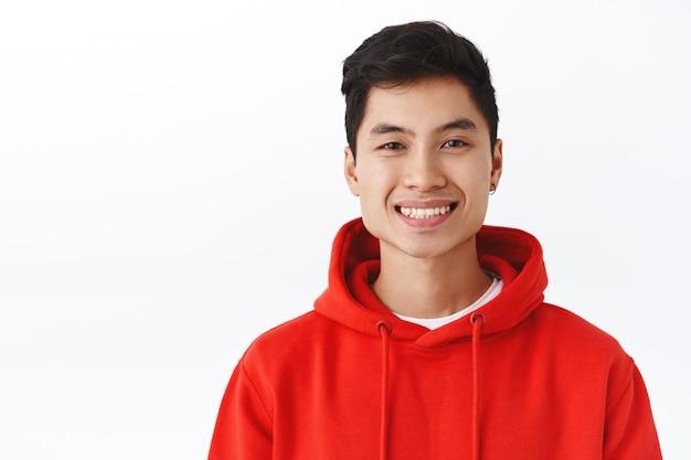 Portrait en gros plan d'un étudiant asiatique enthousiaste et attrayant en sweat à capuche rouge, boucle d'oreille, appareil photo souriant et joyeux, l'air heureux, heureux et satisfait, mur blanc debout. espace de copie