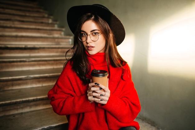 Portrait de gros plan d'étudiante aux cheveux noirs en pull rouge et chapeau, appréciant le café sur le mur des marches.