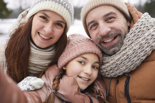 Portrait en gros plan d'une famille heureuse prenant une photo de selfie et souriant à la caméra tout en profitant d'une promenade en plein air ensemble dans la forêt d'hiver