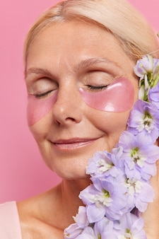 Portrait en gros plan d'une femme d'âge moyen heureuse qui garde les yeux fermés applique des patchs d'hydrogel