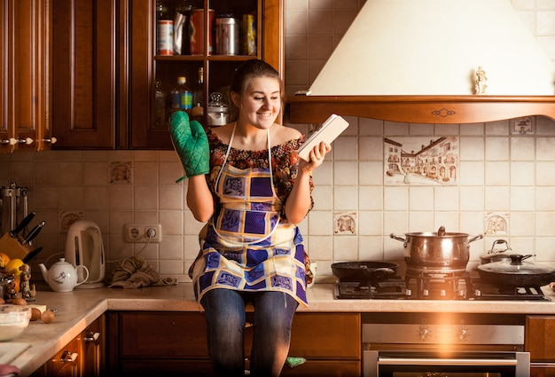 Portrait en gros plan d'une femme au foyer assise sur une table et utilisant une tablette