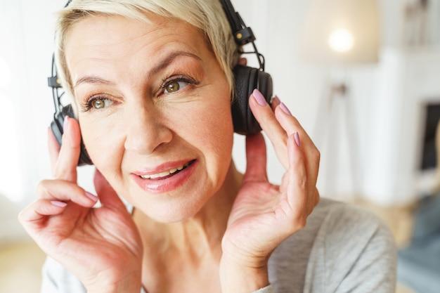 Portrait en gros plan d'une femme blonde senior heureuse dans des écouteurs à la mode, profitant de ses chansons préférées