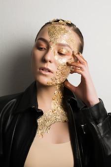 Portrait en gros plan d'une femme brune glamour avec une feuille d'or sur le visage et le cou, portant une veste en cuir