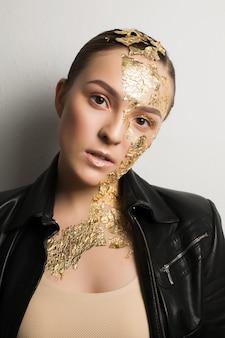 Portrait en gros plan d'une femme brune luxueuse avec une feuille d'or sur le visage et le cou, portant une veste en cuir