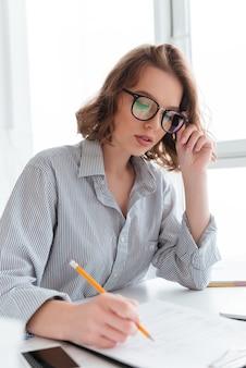 Portrait de gros plan d'une femme brune sérieuse touchant ses lunettes tout en travaillant avec des papiers à la maison