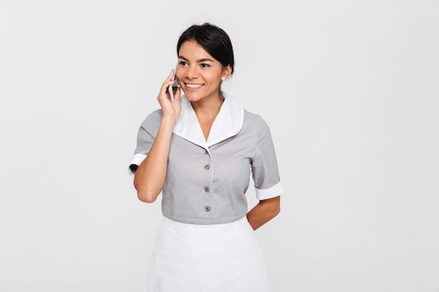 Portrait de gros plan d'une femme brune en uniforme gris parlant sur téléphone mobile