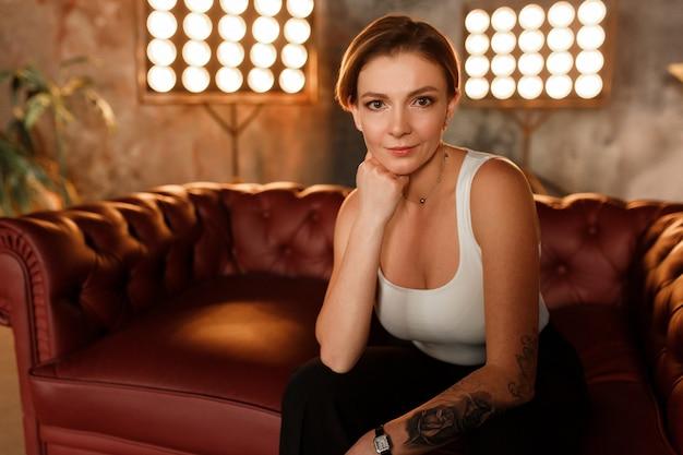 Portrait en gros plan femme sur un canapé en cuir dans une pose expressive, en regardant la caméra.