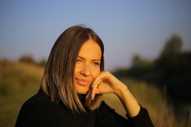 Portrait en gros plan d'une femme confiante et élégante dans un col roulé tenant la main sous le menton