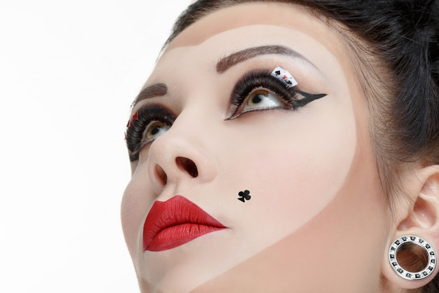 Portrait de gros plan d'une femme avec du maquillage de fantaisie comme carte à jouer.