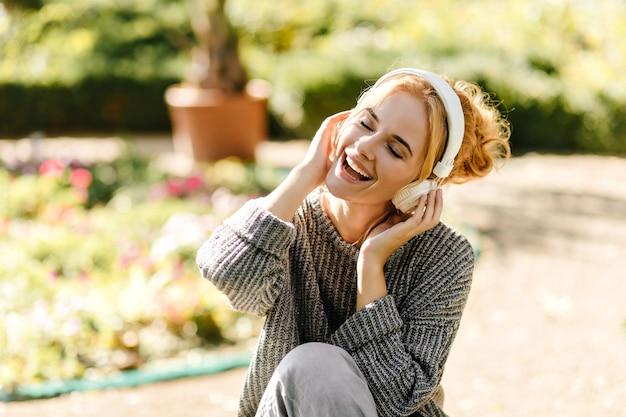 Portrait de gros plan de femme écoutant de la musique de bonne humeur, vêtue d'un pull en tricot gris.