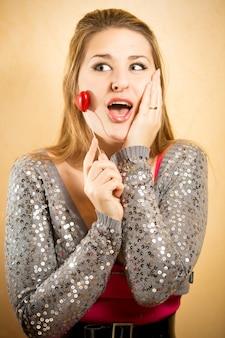 Portrait en gros plan d'une femme excitée tenant un coeur décoratif sur un bâton