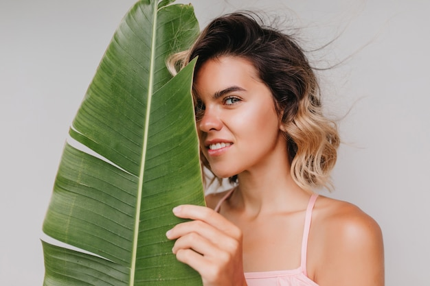 Portrait en gros plan d'une femme intéressée avec une peau bronzée brillante à la recherche. heureuse fille caucasienne aux cheveux courts ondulés isolés.