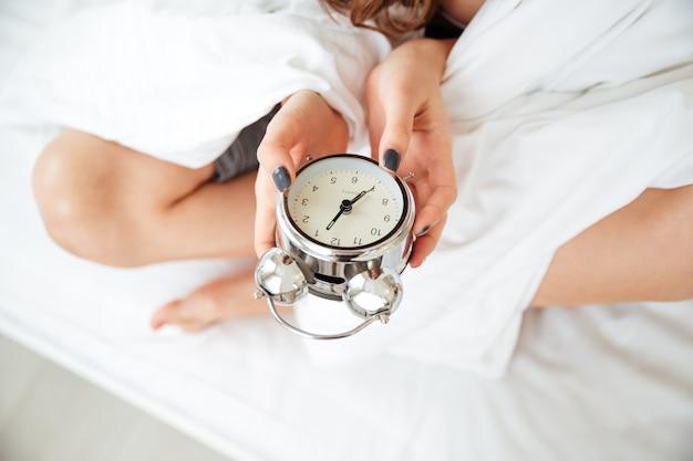 Portrait en gros plan d'une femme mains tenant un réveil sur le lit