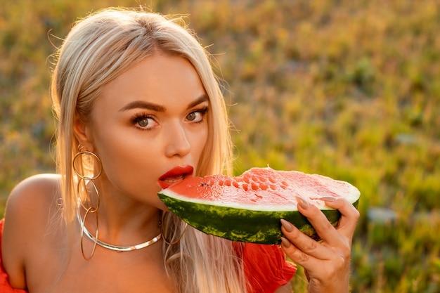Portrait en gros plan d'une femme mordant une pastèque