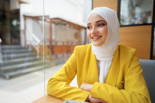 Portrait en gros plan d'une femme musulmane portant un foulard assis dans un café