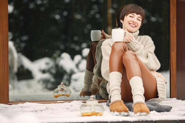 Portrait de gros plan de femme en pull blanc, boire du thé