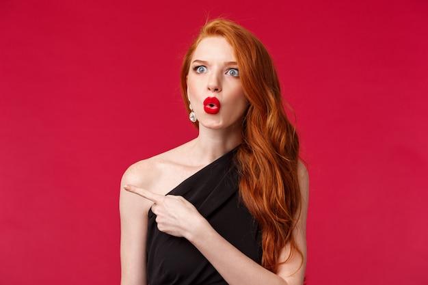 Portrait de gros plan d'une femme rousse séduisante excitée et sans voix impressionnée, vêtue d'une robe noire, d'un rouge à lèvres rouge et d'un maquillage de soirée. regarder surpris dire wow pointant à gauche interrogé