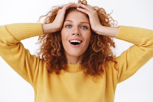 Portrait en gros plan femme rousse souriante heureuse et joyeuse touchant ses cheveux bouclés, souriant et regardant la caméra avec plaisir, entendez quelque chose de surprenant, contente de recevoir de bonnes nouvelles, se sente soulagée