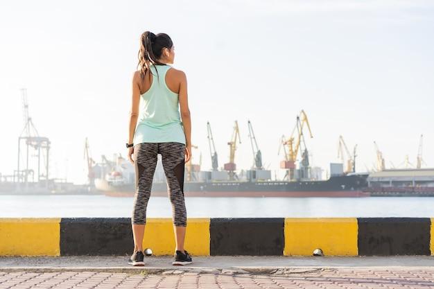 Portrait en gros plan d'une femme sportive assez souriante, tenant une bouteille d'eau tout en écoutant de la musique, en bord de mer en plein air