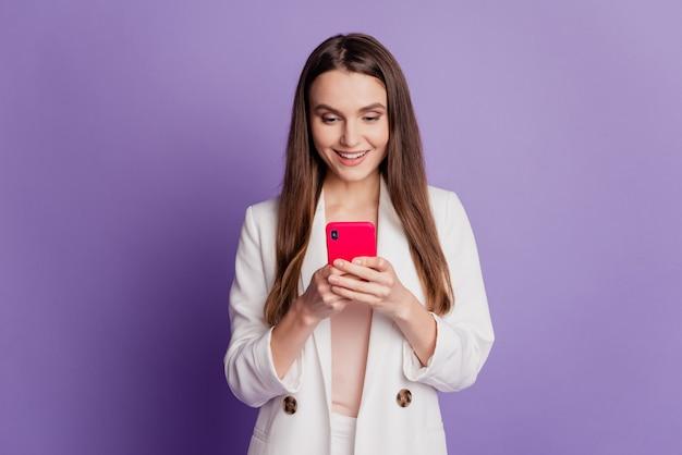 Portrait en gros plan d'une femme tenant un écran de téléphone portant un costume formel posant sur un mur violet