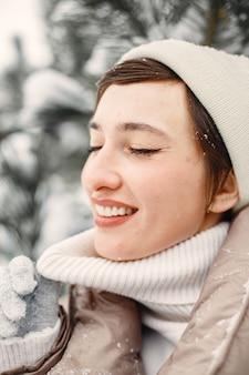 Portrait de gros plan de femme en veste marron dans un parc enneigé