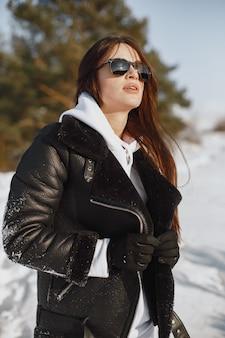 Portrait de gros plan de femme en veste noire. femme debout dans une forêt en jour de neige.