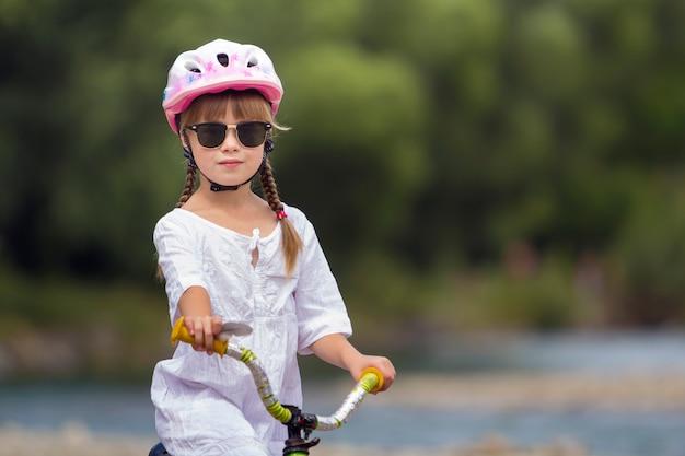 Portrait de gros plan de la fière jolie jeune fille en vêtements blancs, lunettes de soleil avec de longues tresses blondes portant un casque de sécurité rose, vélo d'enfant sur les arbres flous verts d'été copie espace.
