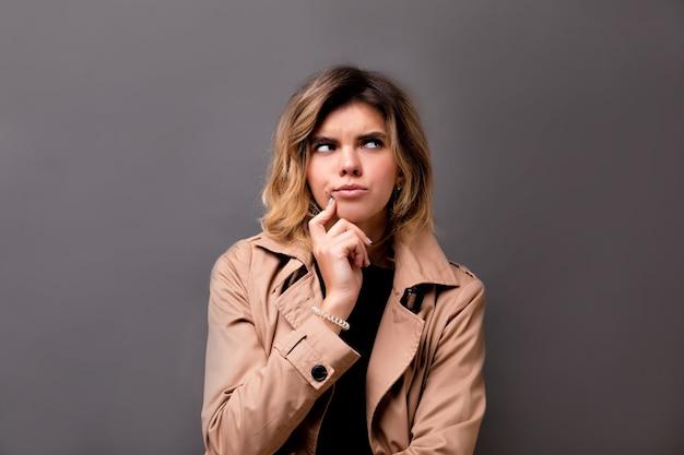 Portrait en gros plan d'une fille au regard réfléchi avec de grands yeux bruns à la recherche de suite. photo intérieure d'une femme européenne étonnée avec des cheveux courts et clairs isolés sur un mur gris.