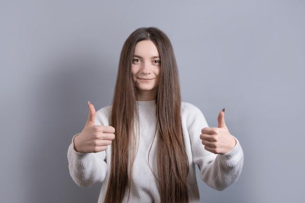 Portrait en gros plan d'une fille aux cheveux noirs satisfaite et impressionnée, laisse des commentaires positifs sur le café ou l'endroit où elle se rend, montre le pouce en l'air et l'approbation, souriant heureux, fond gris.