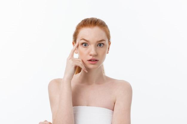 Portrait de gros plan d'une fille belle, fraîche, saine et sensuelle sur fond blanc