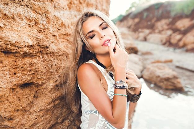 Portrait de gros plan d'une fille blonde sexy aux cheveux longs posant à la caméra sur fond de pierre. elle garde le doigt sur les lèvres et les yeux fermés.