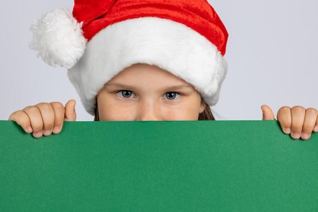 Portrait en gros plan d'une fille dans un chapeau de gnome de noël se cachant derrière une affiche verte noire dans ses mains...