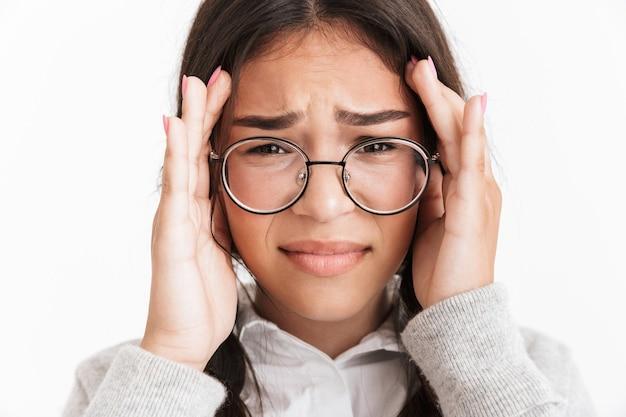 Portrait en gros plan d'une fille effrayée anxieuse portant des lunettes pleurant et couvrant son visage isolé sur un mur blanc