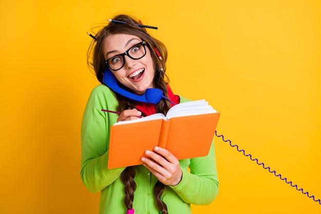 Portrait en gros plan d'une fille extatique gaie assez funky parlant au téléphone, exercice d'écriture isolé sur fond de couleur jaune vif