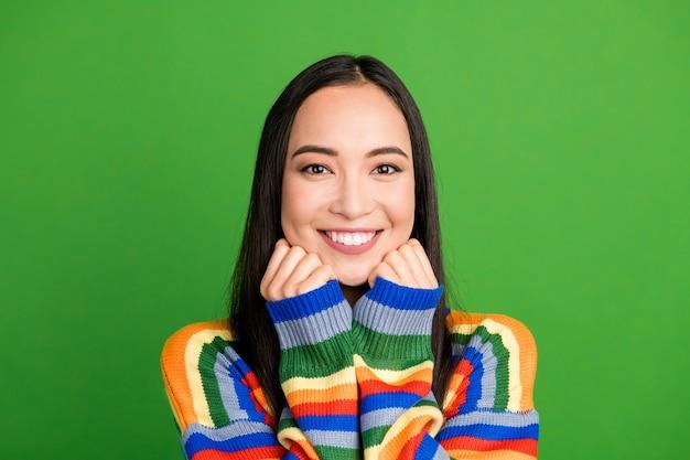 Portrait en gros plan d'une fille joyeuse au contenu attrayant avec des dents blanches au sourire rayonnant isolées sur fond de couleur vert clair