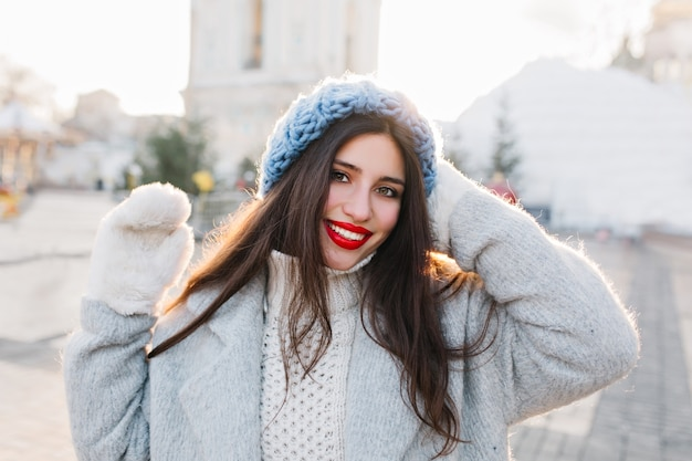 Portrait de gros plan de fille joyeuse aux longs cheveux noirs posant dans la matinée d'hiver sur la ville floue. dame brune en béret bleu bénéficiant d'une séance photo par temps froid.