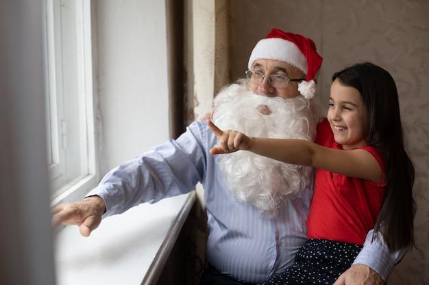 Portrait en gros plan d'une fille joyeuse étreignant le grand-père en couvre-chef. grand-père et petite-fille en chapeaux de père noël