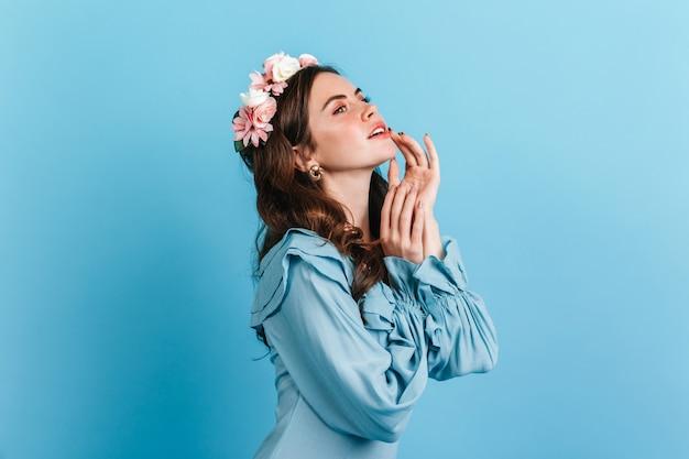 Portrait en gros plan d'une fille sensuelle en chemisier en soie à volants. dame aux fleurs dans les cheveux touchant les lèvres.