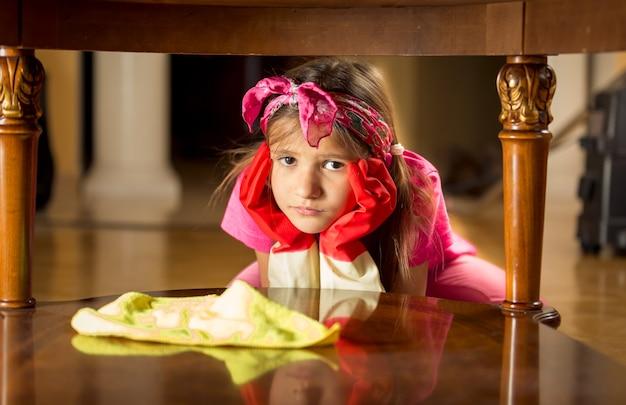 Portrait en gros plan d'une fille triste et fatiguée nettoyant une table en bois