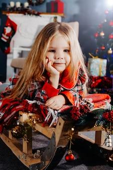 Portrait en gros plan d'une fillette de quatre ans près de l'arbre du nouvel an