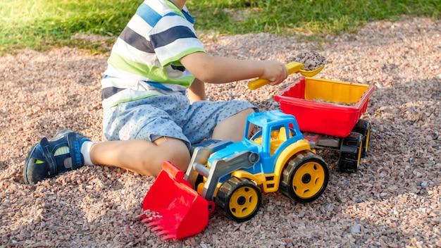 Portrait en gros plan d'un garçon de 3 ans souriant et souriant creusant du sable sur le terrain de jeu avec un camion ou une excavatrice en plastique jouet. enfant jouant et s'amusant au parc en été