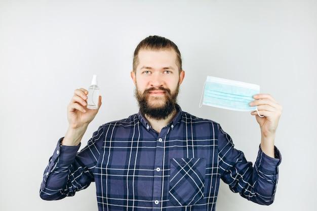 Un portrait en gros plan d'un gars émotif dans un masque médical avec un désinfectant dans ses mains. arrêtez la propagation de l'infection à coronavirus. covid 2019