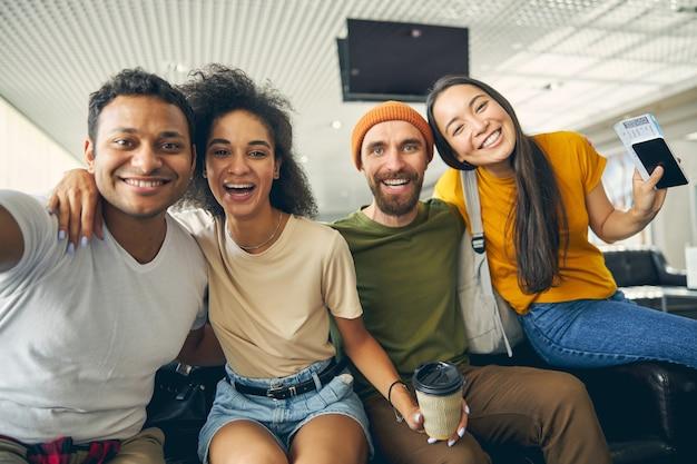 Portrait en gros plan de gens sympathiques s'amusant dans la salle d'embarquement de l'aéroport en regardant la caméra photo
