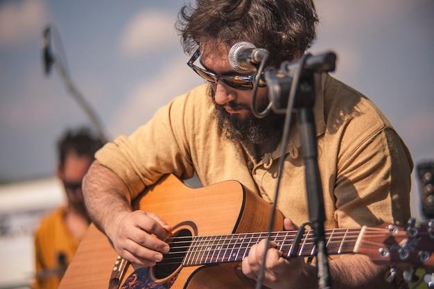 Portrait en gros plan d'un guitariste classique alors qu'il se concentre, il joue sa composition