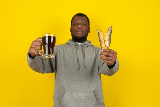 Portrait en gros plan homme barbu afro-américain avec une bière noire dans une main et deux poissons dans l'autre, debout isolé sur un mur jaune
