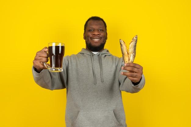 Portrait en gros plan d'un homme barbu avec une bière noire dans une main et deux poissons dans l'autre, se dresse sur un mur jaune.