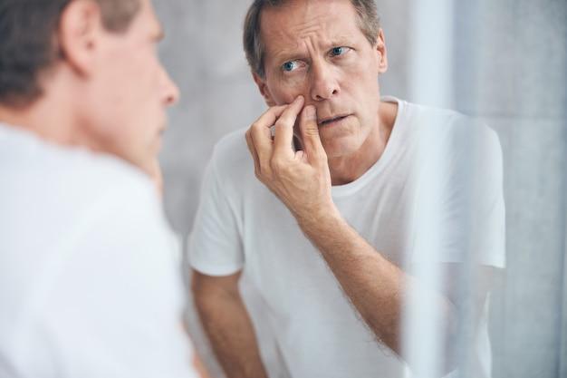 Portrait en gros plan d'un homme faisant un examen de la peau devant le miroir sur le mur
