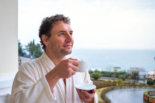 Portrait en gros plan d'un homme heureux dans une robe en tissu éponge blanc qui rencontre le matin avec une tasse de thé ou de café et une belle vue sur la mer. le concept de détente, d'éveil et de santé.