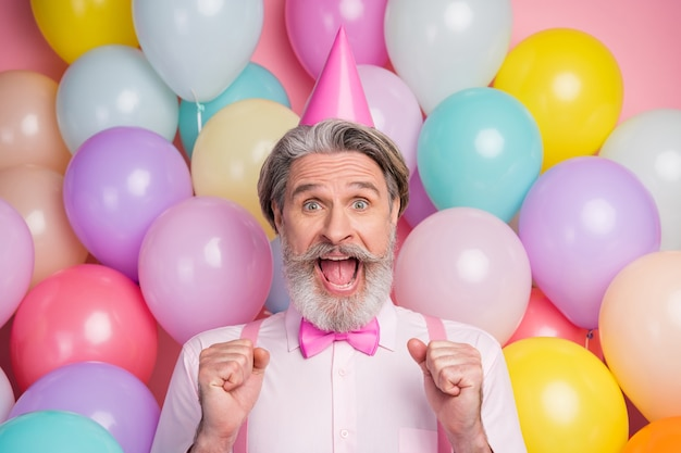 Portrait en gros plan d'un homme mûr s'amusant à célébrer son anniversaire sur un mur rose